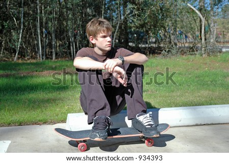 Teen Skateboarder at Rest - stock photo