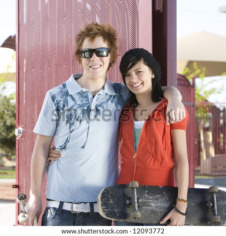 Teen skating couple hangs out at the park - stock photo
