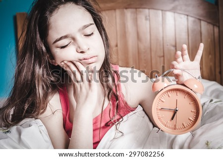 Teen sleepy young girl waking up in bed  - stock photo