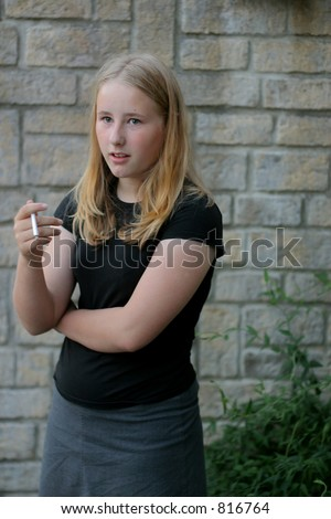 Teen smoking first cigarette -  Soft Focus [set up picture using a stage prop cigarette] - stock photo