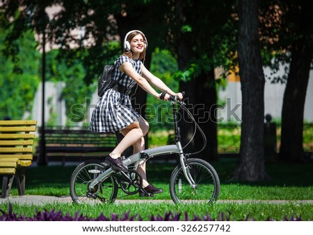 Teen student girl or young woman in plaid dress rides a folding bicycle and listens music in white earphones in the park - stock photo