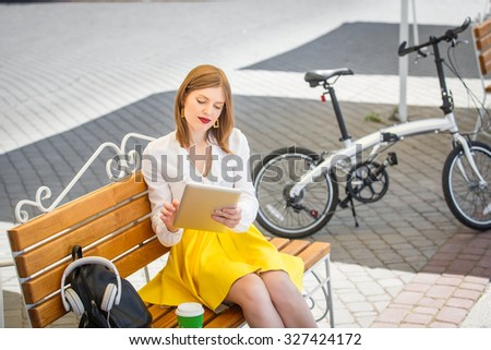 Teen student girl or young woman in yellow skirt and white blouse uses tablet pc sitting on the bench near a folding bicycle in the park - stock photo