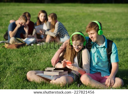 Teen students sitting and listening to mp3 player together - stock photo