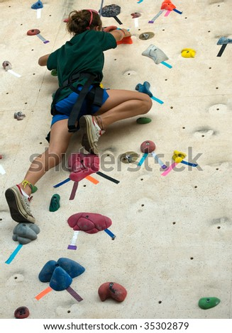 Teen taking a BIG step up an artificial wall - stock photo
