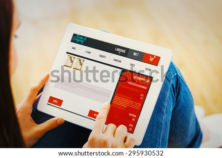 Teen using a tablet pc sitting on the floor against website design - stock photo