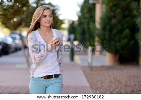 Teen using smartphone. Woman walking on a city street while holding a smartphone.