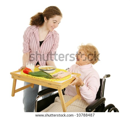 Teen volunteer serving soup to a disabled senior woman.  Isolated on white. - stock photo
