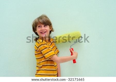 Teen With Roller Against The Light Green Wall. - stock photo