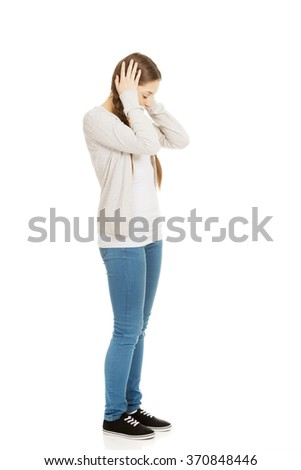 Teen woman covering ears with hands.