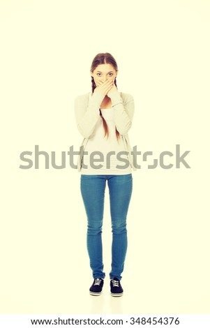 Teen woman covering her mouth with both hands. - stock photo