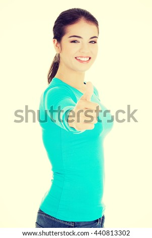 Teen woman gesturing thumbs up - stock photo
