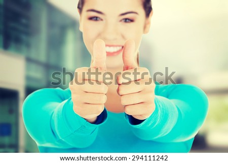 Teen woman in casual clothes gesturing thumbs up - stock photo