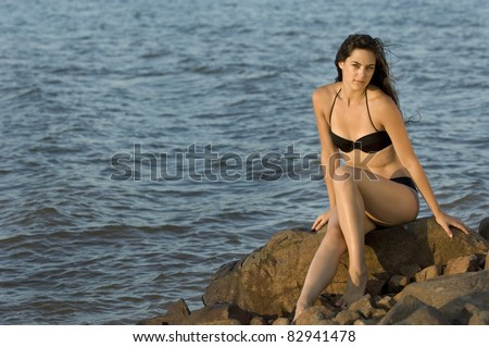 Teen woman in swimsuit sitting on rocks by water at sunset - stock photo