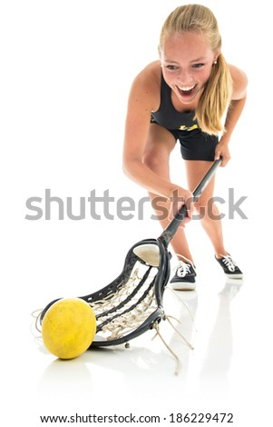 Teen woman playing lacrosse. Exaggerated wide angle on foreground where she scoops up the ball. Studio shot, with white background and reflective floor. - stock photo
