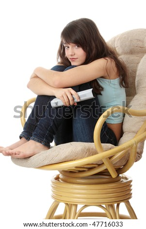 Teen woman watching TV with remote control while sitting on armchair view from TV - stock photo