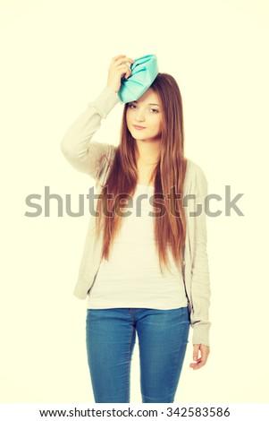 Teen woman with headache and ice bag. - stock photo