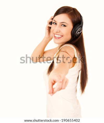 teen woman with headphones pointing on you, white background - stock photo
