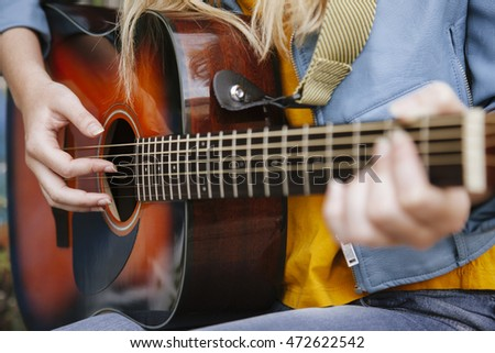 teen woman with her fingers playing acoustic guitar