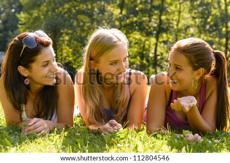 Teen women talking and relaxing in park happy grass friends - stock photo