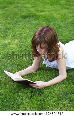 Teen.Young beautiful girl reading a book outdoor - stock photo