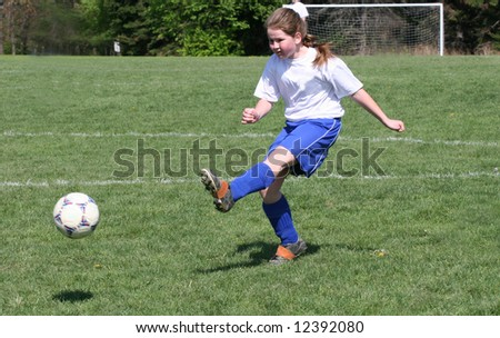 Teen Youth Girl kicking ball in air at soccer game. - stock photo