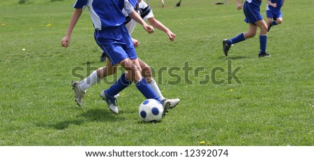 Teen Youth Kicking Soccer Ball at Game - stock photo