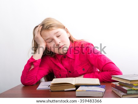 teenag girl sitting at a table in front of her large pile of books. schoolgirl reading a books and doing homework - stock photo