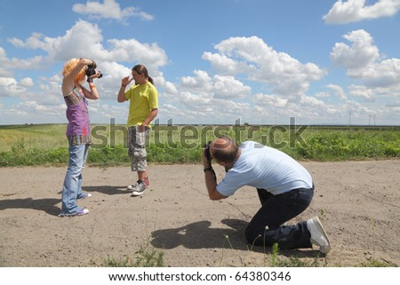 Teenage and middle age photographers photographing at location - stock photo