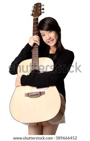 Teenage asain girl hugging her acoustic guitar, Isolated over white