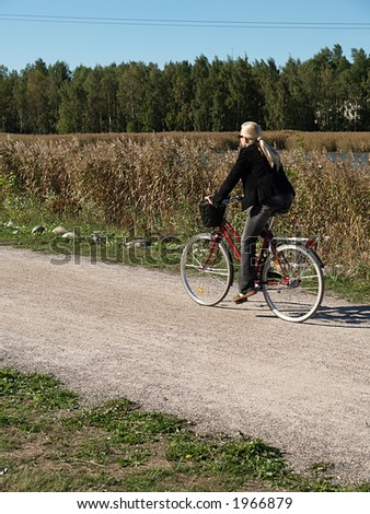 Teenage blond girl bicycling, view - stock photo