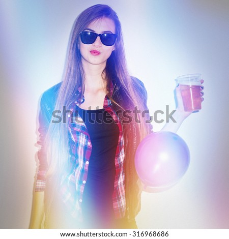 Teenage blonde girl at the party wearing sunglasses, red plaid shirt and leather jacket holding a glass. Light leak effects, matte and colorful filter applied, square format, with grain. - stock photo