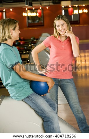 Teenage boy and girl in a bowling alley, flirting and exchanging phone numbers - stock photo