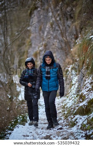 Teenage boy and his mother hiking on a winter trail in the mountains