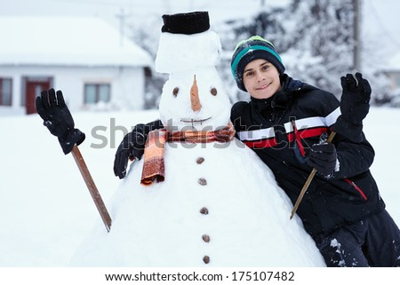 Teenage boy building a snowman in the countryside - stock photo
