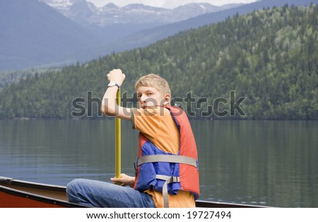Teenage boy canoeing, Canada - stock photo