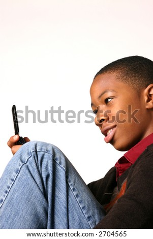 Teenage boy contemplates cell phone in his hand - stock photo