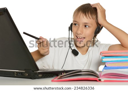 Teenage boy doing homework with laptop on a white background - stock photo