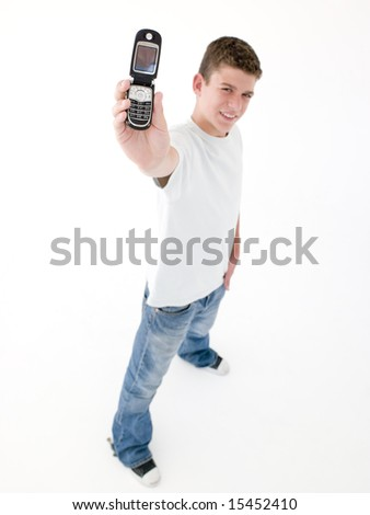 Teenage boy holding up cellular phone and smiling - stock photo