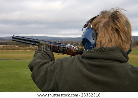 Teenage boy holds the gun to the left to fire a at the clay pigeon - stock photo