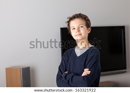 Teenage Boy in a modern living room with a flat-screen TV in the background
