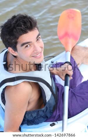 Teenage boy in canoe - stock photo