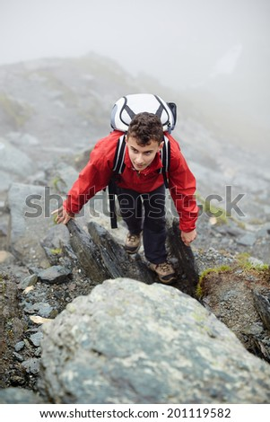 Teenage boy in rain coat and mountaineer equipment hiking on a trail in a rocky mountain