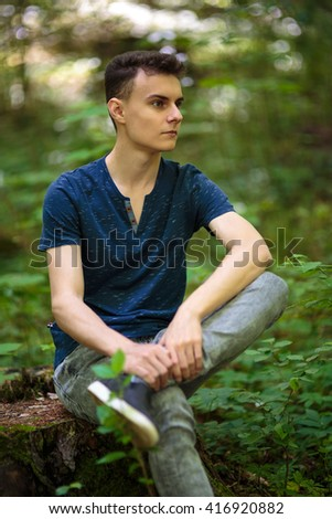 Teenage boy in the park in various postures - stock photo