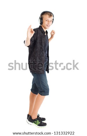 Teenage boy is wearing a black shirt, denim shorts and sneakers with headphones. Boy is showing OK sign. Studio shot, isolated on white background. - stock photo