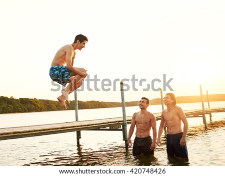 Teenage boy jumping into a lake from a old pier bridge watched by two of his friends as they relax on summer camp, high key sunset or sunrise background - stock photo