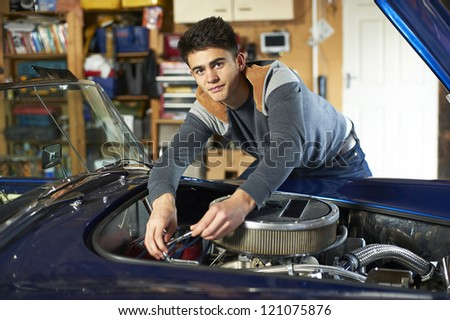 teenage boy leaning over the engine of a classic car in garage holding wrench - stock photo
