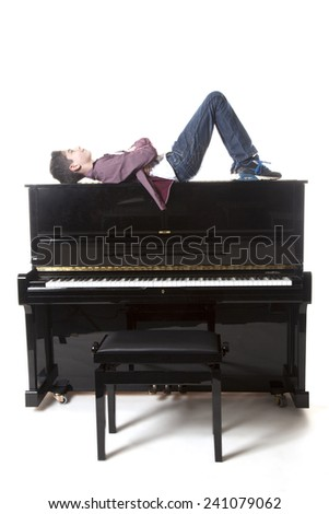 teenage boy lies upon upright piano in studio with white background - stock photo