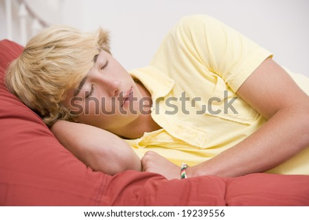Teenage boy Lying In Bed Asleep - stock photo