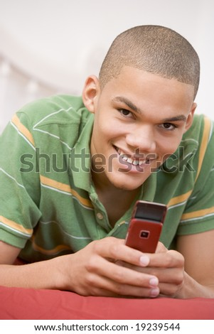 Teenage boy Lying On Bed Texting - stock photo