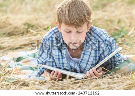 Teenage boy lying with a book outdoor - stock photo